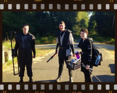 The cast with finished costumes carrying stuff down to the location.